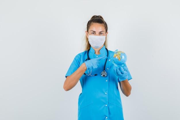 Kobieta Lekarz Wskazując Palcem Na świecie W Niebieskim Mundurze Darmowe Zdjęcia