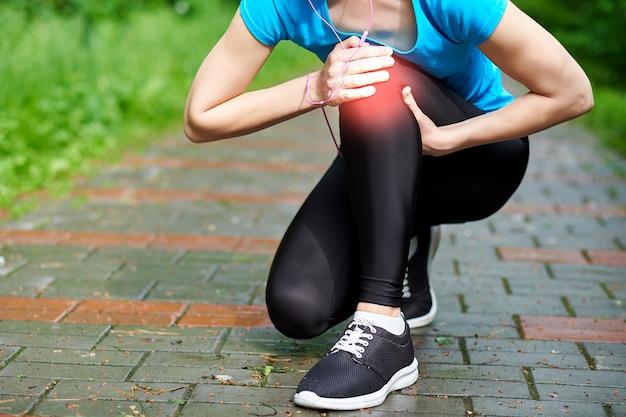 Kobieta Lekkoatletka Lekkoatletka Dotykając Kolana W Bólu, Fitness Kobieta Działa W Lato Park. Pojęcie Zdrowego Stylu życia I Sportu Premium Zdjęcia