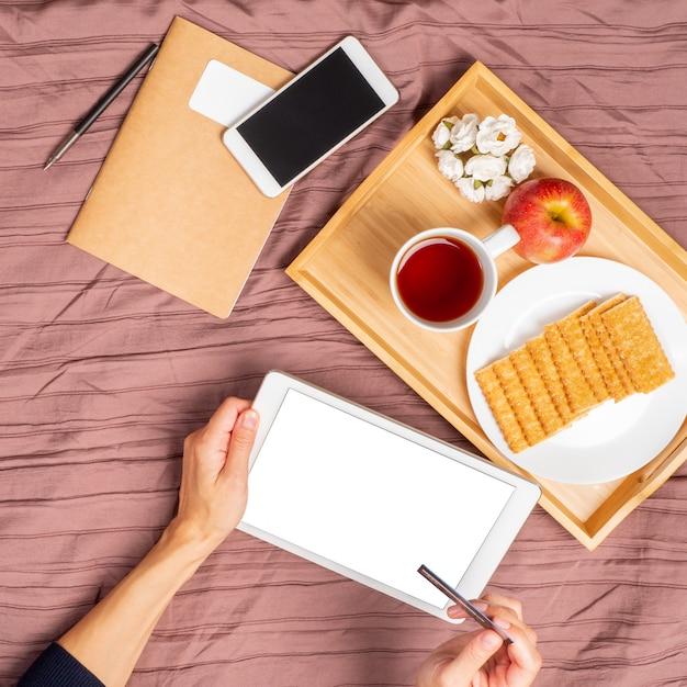 Kobieta leżąc na łóżku, picie herbaty i patrząc na tabletki, płacić za zakupy, zakupy online. Premium Zdjęcia