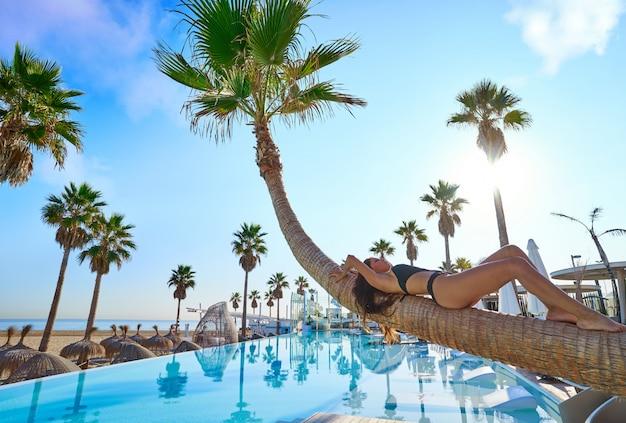 Kobieta leży na basenie wygięty pień drzewa palmowego Premium Zdjęcia