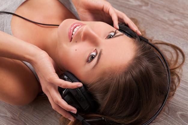 Kobieta leży na podłodze ze słuchawkami Darmowe Zdjęcia
