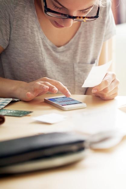 Kobieta liczenia pieniędzy na swoim telefonie Darmowe Zdjęcia