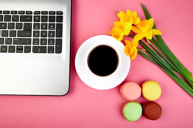 Kobieta lub kobiecy obszar roboczy z notatnikiem, kawą, makaronikami i kwiatami Premium Zdjęcia