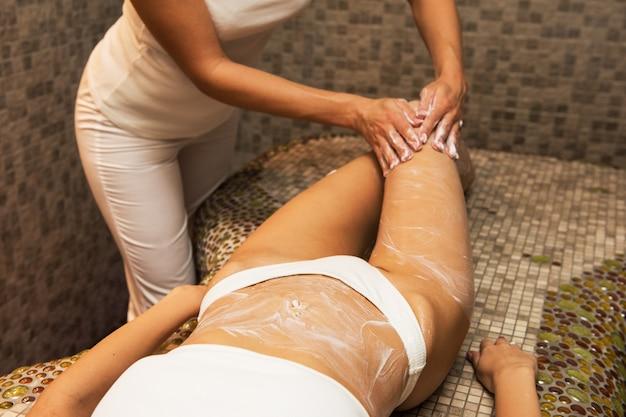 Kobieta ma masaż z śmietanką przy zdrojem Premium Zdjęcia