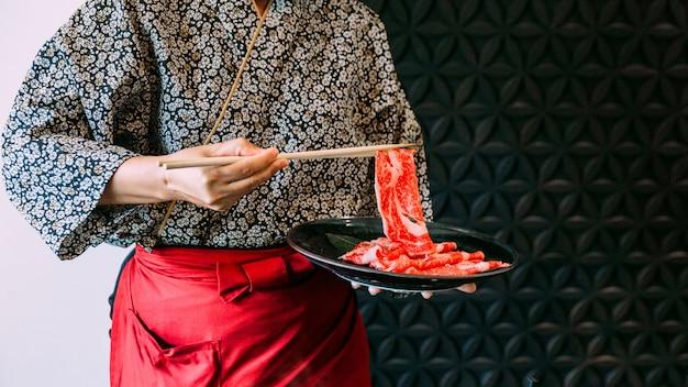Kobieta ma na sobie kimono gospodarstwa rzadkie plasterek wagyu wołowiny pałeczkami Premium Zdjęcia