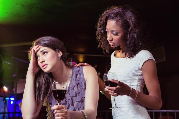 Kobieta ma napoje i pociesza jej przygnębionego przyjaciela w barze Premium Zdjęcia
