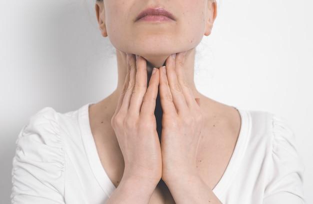 Kobieta Ma Zaburzenia Tarczycy. Ból Gardła. Zapalone Gruczoły. Premium Zdjęcia