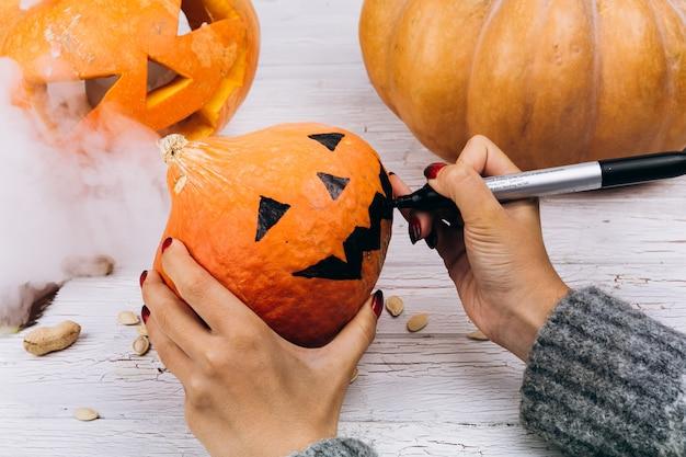 Kobieta Maluje Twarz Na Pomarańczowej Bani Dla Halloween Darmowe Zdjęcia