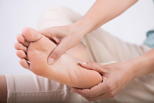 Kobieta masuje jej bolesną stopę Premium Zdjęcia