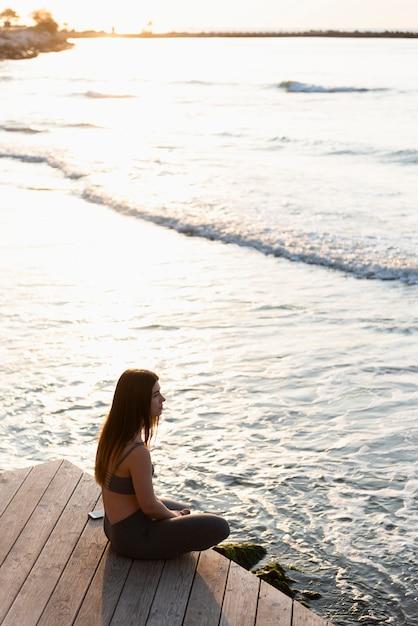 Kobieta Medytując Nad Morzem Darmowe Zdjęcia