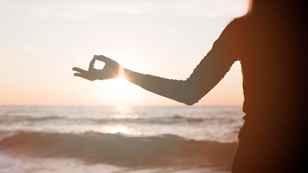 Kobieta, Medytując O Zachodzie Słońca Na Plaży Darmowe Zdjęcia
