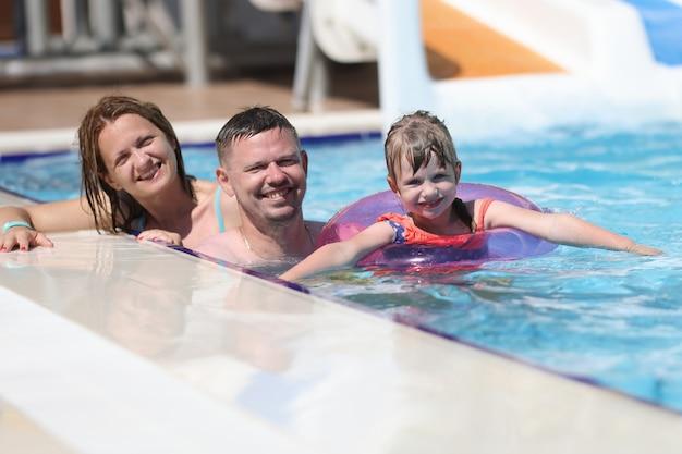 Kobieta, Mężczyzna I Córka Uśmiechają Się Razem. Rodzina Pływać W Basenie W Słońcu. Premium Zdjęcia