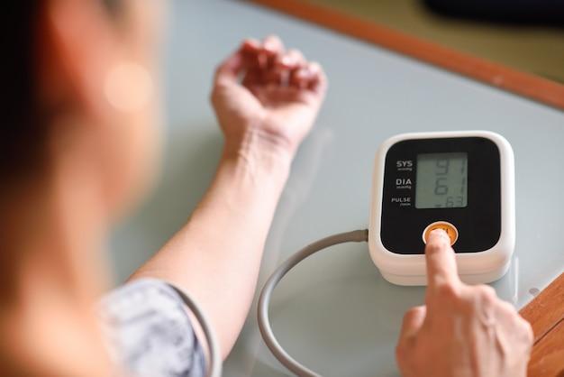 Kobieta mierzy jej własne ciśnienie krwi w domu. Premium Zdjęcia