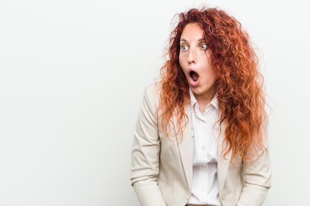 Kobieta Młody Biznes Rudy Naturalny Na Białym Tle Jest W Szoku Z Powodu Czegoś, Co Widziała. Premium Zdjęcia