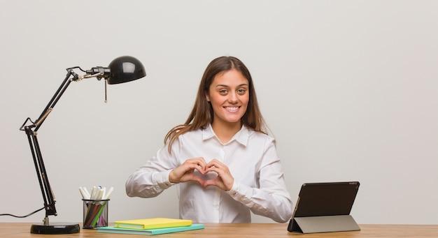 Kobieta Młody Student Pracuje Na Biurku, Robi Kształt Serca Rękami Premium Zdjęcia