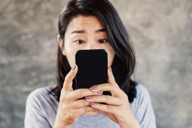 Kobieta Mruży Oczy, Oglądając Telefon Komórkowy Premium Zdjęcia