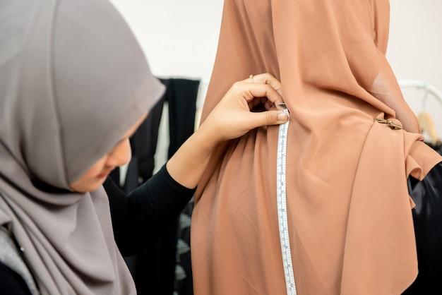 Kobieta muzułmański projektant pomiaru wielkości ubrania Premium Zdjęcia