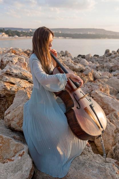 Kobieta Muzyk Gra Na Wiolonczeli O Zachodzie Słońca Na Skałach Darmowe Zdjęcia