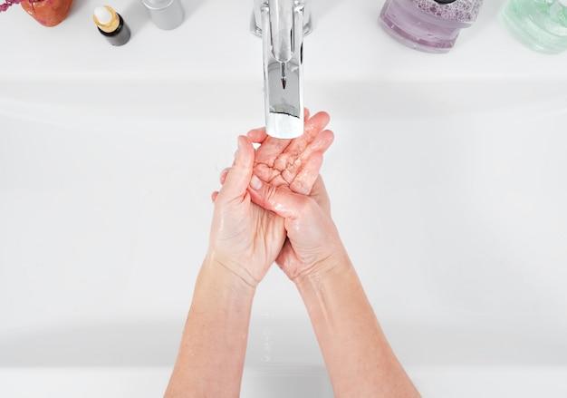 Kobieta Myje Ręce Pod Bieżącą Wodą. Pojęcie Higieny, Widok Z Góry, Opieka Zdrowotna. Higiena Osobista I Pielęgnacja Ciała Premium Zdjęcia