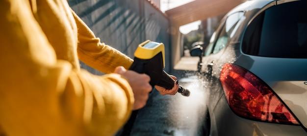 Kobieta Myje Swój Samochód Z Myjką Ciśnieniową Premium Zdjęcia