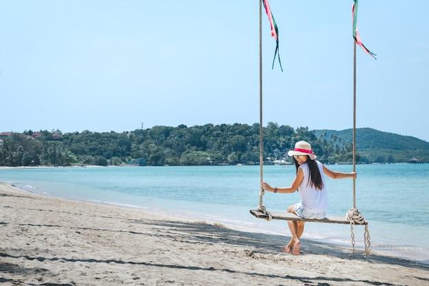 Kobieta na huśtawce w plaży Premium Zdjęcia