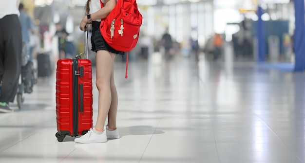 Kobieta Na Lotnisku Z Czerwonym Bagażem Premium Zdjęcia