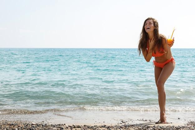 Kobieta Na Plaży Przy Lampce Koktajlu Premium Zdjęcia