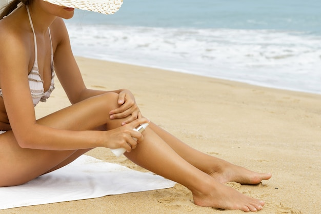 Kobieta Na Plaży Stosując Spray Do Oprysków Na Ciele Premium Zdjęcia