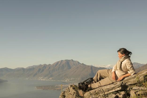 Kobieta Na Skale Z Pięknym Widokiem Na Góry W Pobliżu Brzegu Morza Darmowe Zdjęcia