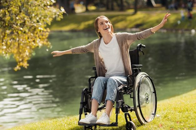 Kobieta na wózku inwalidzkim siedzi na brzegu jeziora. Premium Zdjęcia