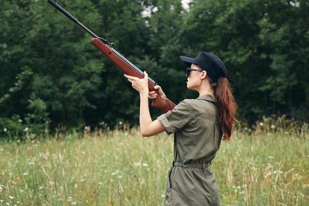 Kobieta Na Zewnątrz Trzyma Broń W Celu Polowania Na Zielony Kombinezon Przycięty Widok Premium Zdjęcia