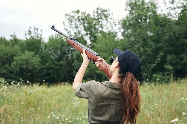 Kobieta Na Zewnątrz Trzymając Pistolet W Górę Wzroku Polowanie Na Zielone Liście Przycięty Widok Premium Zdjęcia
