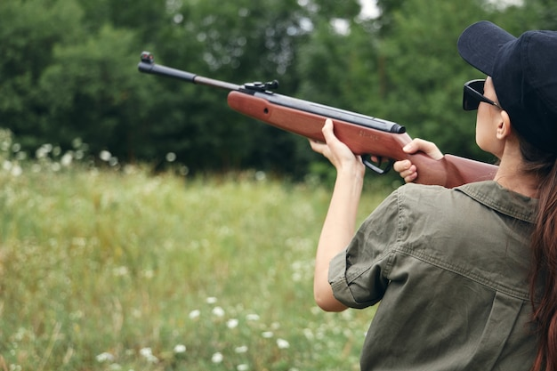 Kobieta Na Zewnątrz, Trzymając Pistolet W Pobliżu Wzroku Głowy Polowanie Na Zielone Liście Premium Zdjęcia