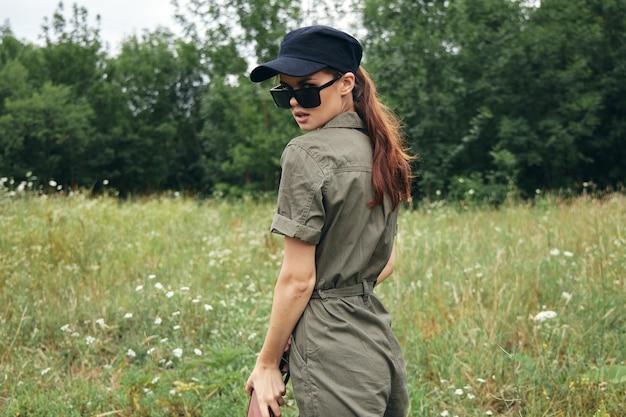 Kobieta Na Zewnątrz Zielony Kombinezon Okulary Przeciwsłoneczne Czarna Czapka Premium Zdjęcia
