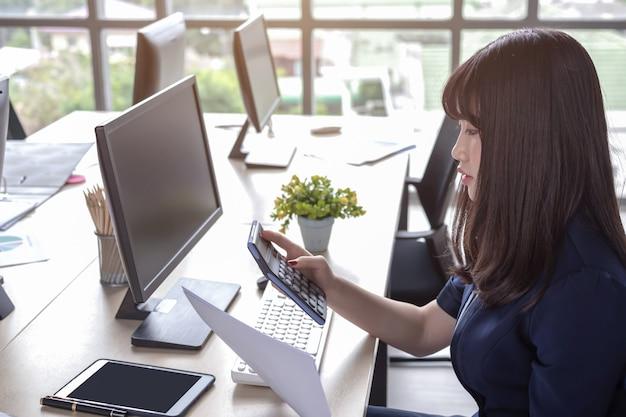Kobieta naciska kalkulator na biurku Premium Zdjęcia