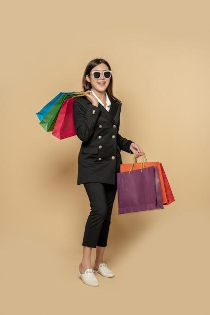 Kobieta Nosi Ciemne Ubrania I Okulary, A Także Wiele Toreb, Aby Iść Na Zakupy Darmowe Zdjęcia