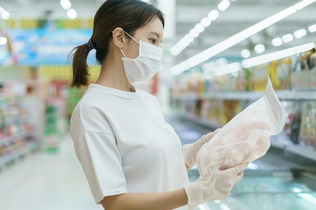 Kobieta Nosi Maskę Chirurgiczną I Rękawiczki, Wybierając Mrożone Ryby W Supermarkecie Po Pandemii Koronawirusa. Premium Zdjęcia