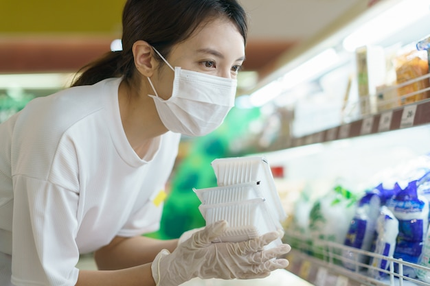 Kobieta Nosi Maskę Chirurgiczną I Rękawiczki, Wybierając Tofu W Supermarkecie Po Pandemii Koronawirusa. Premium Zdjęcia