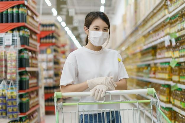 Kobieta Nosi Maskę Chirurgiczną I Rękawiczki Z Wózka Na Zakupy, Robi Zakupy Podczas Pandemii Coronavirus. Premium Zdjęcia