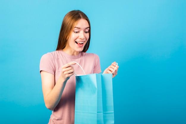 Kobieta o średnim ujęciu patrząc na zakupione przedmioty Darmowe Zdjęcia