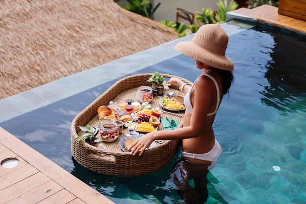 Kobieta O Tropikalne Zdrowe śniadanie W Willi Na Pływającym Stole Darmowe Zdjęcia
