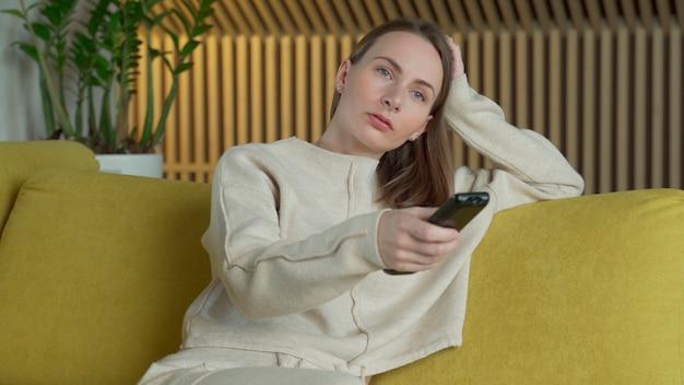 Kobieta Ogląda Filmy Na Ekranie Telewizora W Swoim Domu, Przełącza Kanały Pilotem Siedząc Na żółtej Sofie W Salonie Premium Zdjęcia