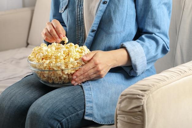 Kobieta Oglądając Film Na Kanapie I Jeść Popcorn. Jedzenie Do Oglądania Filmów Premium Zdjęcia