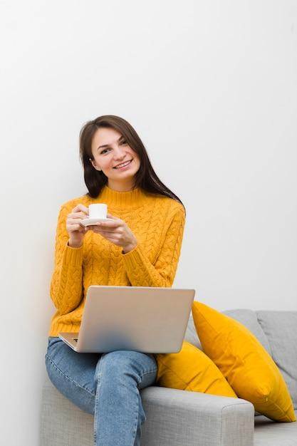 Kobieta Ono Uśmiecha Się Podczas Gdy Siedzący Na Kanapie I Trzymający Filiżankę Kawy Darmowe Zdjęcia