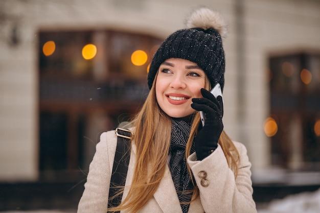 Kobieta opowiada na telefonie na zewnątrz kawiarni Darmowe Zdjęcia