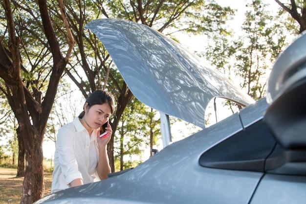 Kobieta, patrząc na podziale silnika samochodu na ulicy. otwieranie kaptura i wołanie o pomoc w ce Premium Zdjęcia