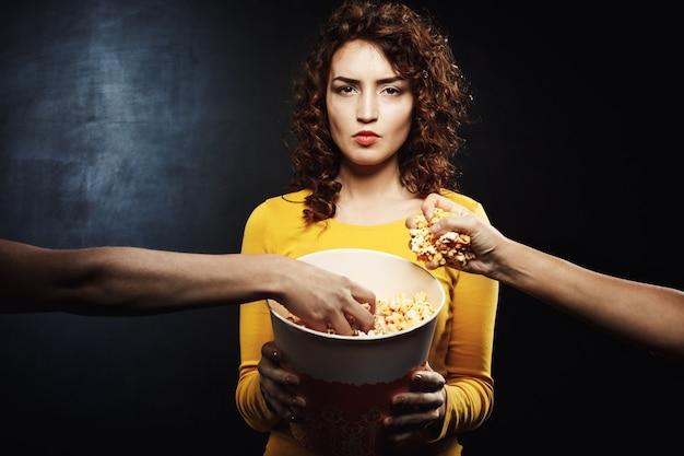 Kobieta Patrząc Prosto Trzymając Wiadro Popcornu, Podczas Gdy Przyjaciele Chwytają Jedzenie Darmowe Zdjęcia