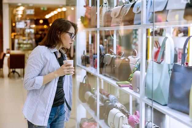 Kobieta patrzeje gablotę wystawową z torbami i akcesoriami Premium Zdjęcia