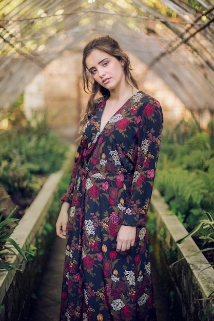 Kobieta patrzeje kamerę w kwiecistej sukni Darmowe Zdjęcia
