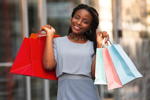 Kobieta patrzeje kamerę z torba na zakupy Darmowe Zdjęcia